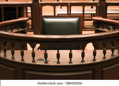 A witness stand with a black seat in the court room in front of tribunal when witness testify of evidence to judge, they will sit at here for testimony of witnesses, it is vintage or retro style