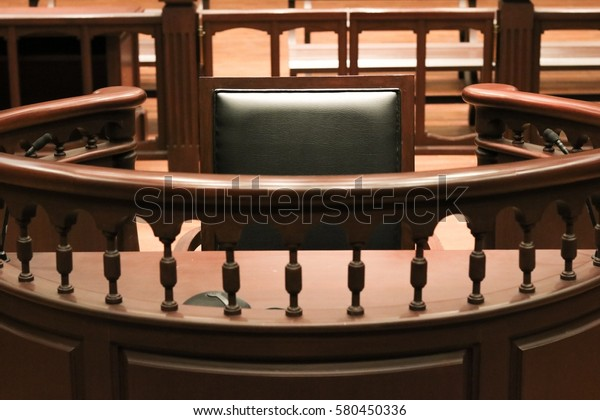 A witness stand with a black seat in the court room infront of tribunal when witness testify of evidence to judge, they will sit at here for testimony of witnesses, it is vintage or retro style