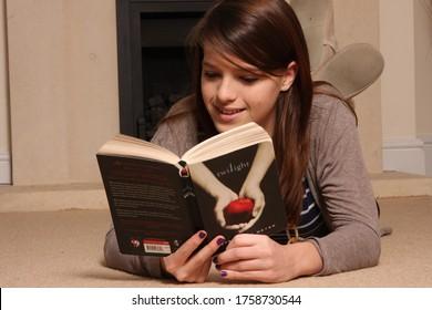 Witney Oxfordshire, UK 02 15 2010 A teenage girl reading the novel Twilight
