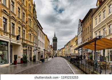 Wittenberg / Germany - February 26th 2017: Old street and buildings in Wittenberg, with All Saints' Church (Schlosskirche ), where the Ninety-five Theses were posted by Martin Luther in 1517.
