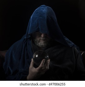 Wizard with beard and blue robe holding crystal ball