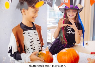 Wizard costume. Beaming smiling girl wearing bright and black wizard Halloween suit attending funny party