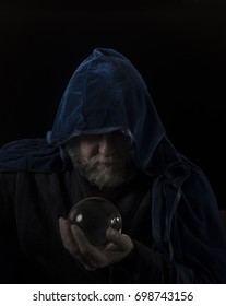Wizard with crystal ball in blue hooded cloak