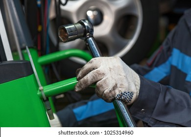 The wizard holds the adjustable wrench. The man is repairing the disc brake machine, close-up. Disk brake repair in the car.