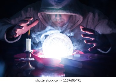 Wizard with hood and lights smoke magic crystal ball on desk with candle in candlestick and old books predicting the future by looking into ball and holding hand above tools. Close up, selective focus