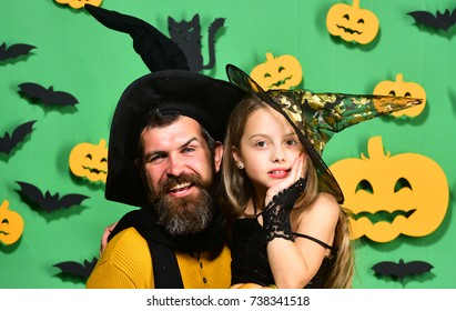 Wizard and little witch in black hats hug. Halloween party and celebration concept. Father and daughter in Halloween costumes. Girl and bearded man with happy faces on green background with decor