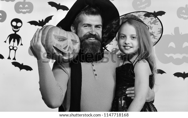 Wizard and little witch in black hats hold pumpkin and hug. Girl and bearded man with happy faces on white background with decor. Halloween party and celebration concept. Dad and daughter in costumes.