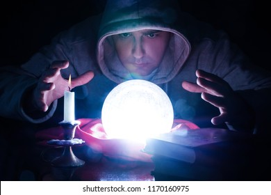 Wizard with magic glowing orb and hand holding above a glass of light, candle and candle stick and book on desk. Sorcerer who predicts destiny. Halloween concept. Close up, selective focus