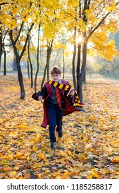 Wizard, Magic wand, cute boy in round glasses, scarf, costume is running in the autumn park. Cosplay, Halloween costume