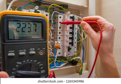 The wizard measures the voltage in the home network using a voltmeter.