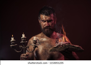 Wizard, sorcerer, warlock. Hipster man with book and candles burning on purple background. Magic spell, enchantment, witchcraft. Halloween holidays celebration. Might, mystic knowledge