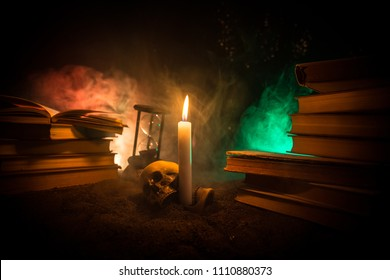 Wizard's Desk. A desk lit by candle light. A human skull, old books on sand surface. Halloween still-life background with a different elements on dark toned foggy background. Selective focus