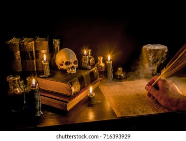 Wizard's Desk. A desk lit by candle light. A human skull, old books, a goblet, and potion bottles also present. A hand writes with a feather quill pen. Thick fog flows from a goblet. Focus on skull.