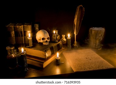 Wizard's Desk. A desk lit by candle light. A human skull, old books, a goblet, and potion bottles are present. Thick fog flows from the goblet onto parchment paper with arcane writing. Focus on skull.