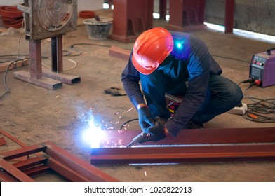 Woeker in orange safety helmet welding iron without mask