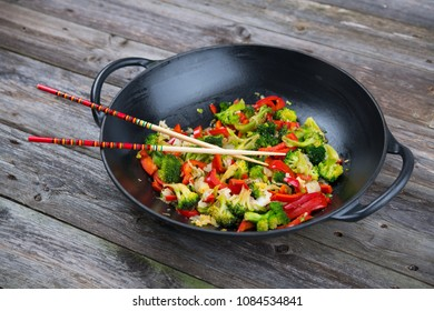 wok with colorful vegetables and chopsticks on wooden ground