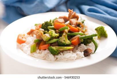 wok fried chicken stir fry with rice and chinese vegetables