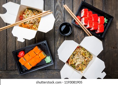 Wok noodles Udon and rice with seafood and chicken in a box and sushi on black background. With chopsticks and sauce. Asian food to go