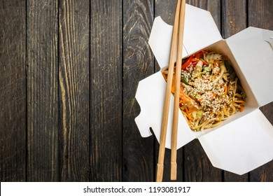 Wok noodles Udon and rice with seafood and chicken in a box on black background. With chopsticks and sauce. Asian food to go