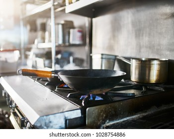 wok on gas stove getting hot in commercial restaurant kitchen