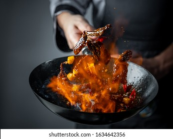 Wok pan cooking asian food with fire flames  and flaming meat and vegetables. Hotel professional service food photo concept. Cooking recipe by chef menu.