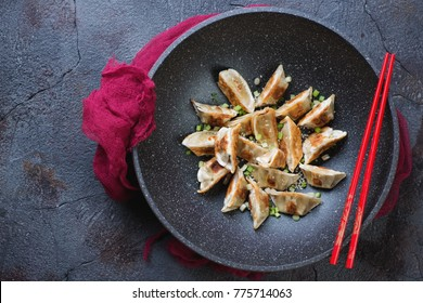Wok pan with fried gyoza dumplings, view from above on a grey stone background, horizontal shot with copyspace