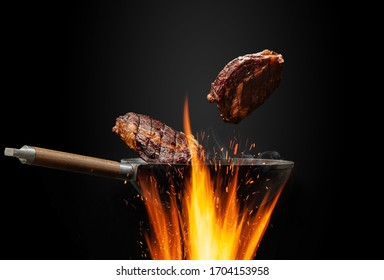 Wok pan with smoke above fire is frying two beef steaks against black studio background. Cooking concept. Close up