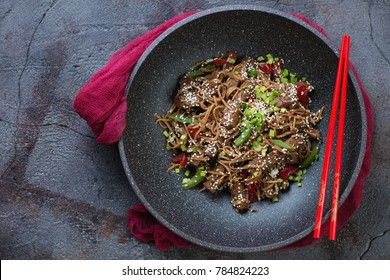 Wok pan with stir-fried yakisoba and beef meat, top view on a cracked asphalt background, horizontal shot with space