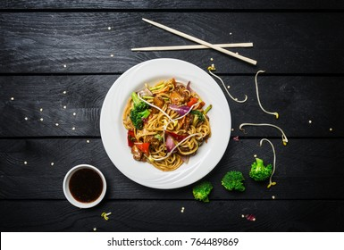 Wok. Udon stir fry noodles with chicken and vegetables in a white plate on black wooden background. With chopsticks and sauce