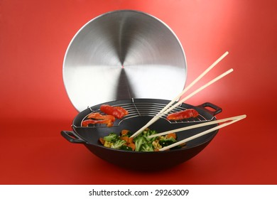 Wok with vegetables and lid on a red background
