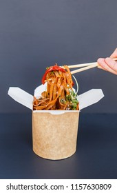 Wok vegetarian noodles in the delivery box on the dark background