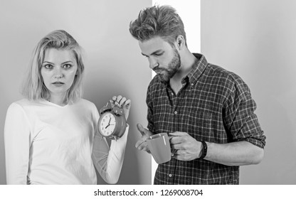 Woke up too late. I am going late for work. Couple in love overslept morning alarm clock. Woman and man sleepy tousled hair drink morning coffee. Couple sleepy faces late for work.