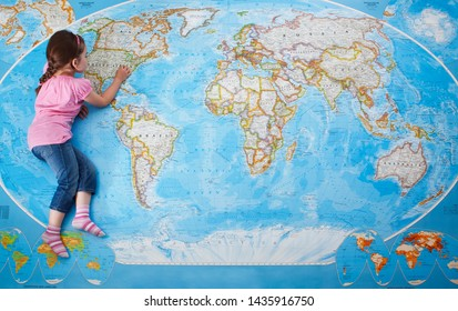 WOKING / ENGLAND :  JUNE 2011 Top view of a young caucasian girl laying on a large map of the world