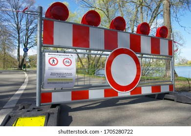 Wolfsburg, Germany- 04/15/2020: Prohibition sign and red and white barrier tape and roadblock  at a locked pond during the Corona crisis in Germany