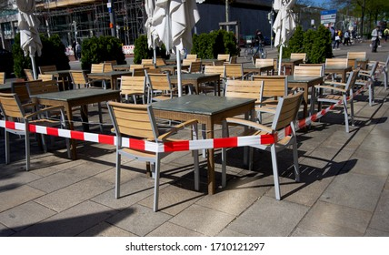 Wolfsburg, Germany- 04/21/2020: stretched security tape at tables to keep social distance to slow down a spread of COVID-19 coronavirus in a store