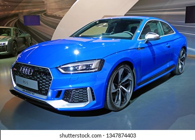 "WOLFSBURG, GERMANY - March 22, 2019: Audi RS5 closeup frontside with lights and logo in showroom ""Autostadt Wolfsburg"""