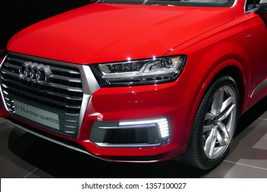 "WOLFSBURG, GERMANY - March 22, 2019: Audi Q7 e-tron quattro closeup frontside with lights on and logo in showroom ""Autostadt Wolfsburg"""