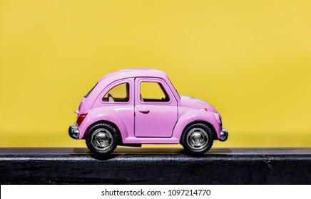 Wolfsburg, Germany - May 10, 2018: miniature pink car  on yellow background