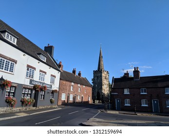 WOLLATON, ENGLAND - SEPTEMBER 28, ‎2018: The centre of pretty Wollaton village in Nottinghamshire, UK, with St Leonard's Church in the background and several listed cottages, under a blue autumn sky