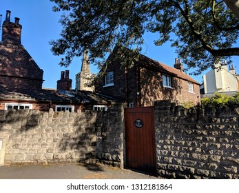 WOLLATON, ENGLAND - SEPTEMBER 28, ‎2018: A row of traditional red brick 18th century cottages in the centre of pretty Wollaton village in Nottinghamshire, UK, under a blue autumn sky