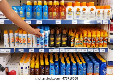 WOLVEGA, NETHERLANDS - AUGUST 26, 2016: Customer selecting Sunscreen, Lotion and Tanning oil spray products in a Action Superstore. Action is a Dutch discount store-chain.