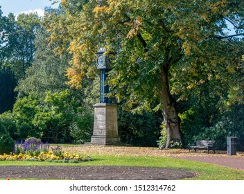 Wolverhampton West Park's cast iron clock tower covered by autumn trees. The clock tower was presented to the town in 1883.