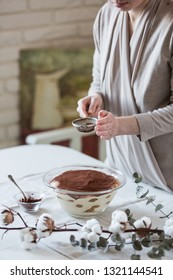 A womam powdering tiramisu dessert in round glass bowl with cocoa powder on white and light kitchen.