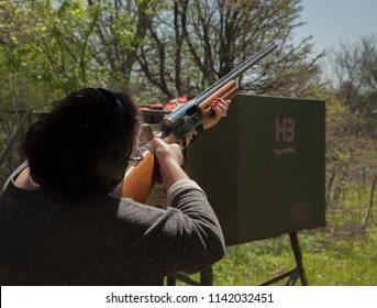 Woman with a 12-gauge shotgun takes aim at a clay pigeon at a skeet shooting practice range. Color, horizontal image, with space for copy.