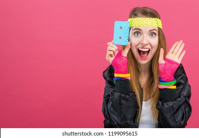 Woman in 1980's fashion holding a cassette tape on a pink background