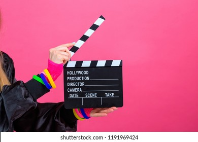 Woman in 1980's fashion holding a film movie slate board clipper on a pink background