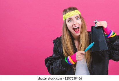 Woman in 1980's fashion playing a cowbell on a pink background