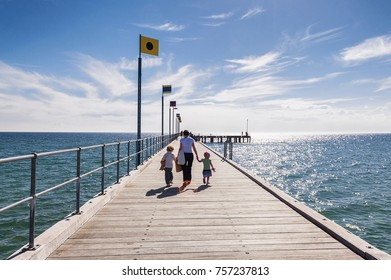 A woman and 2 young girls walking on the pier at the beach holding hands