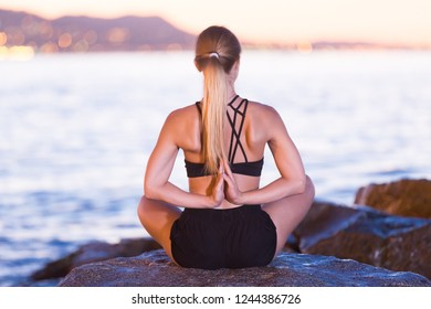 Woman 25-35 years old is meditating on a rock near sea at the dawn.