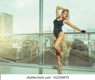 Woman in 30s posing wearing tight bodysuit lingerie and high heels in fron of large windows with urban scenery behind. Toned image.